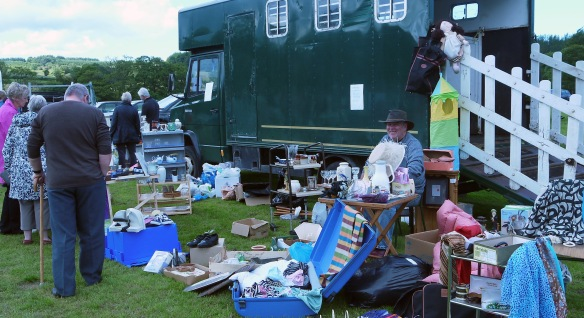 Sitting in front of horsebox with a mass of stuff for sale
